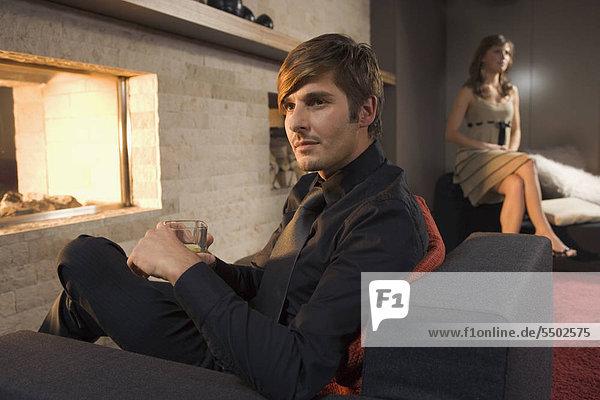 Junger Mann am Kamin  Frau im Hintergrund