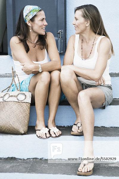 Zwei Frauen mittleren Alters sitzen auf Schritte und Blick auf einander
