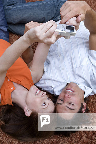 Portrait of couple looking at their digital camera while laying on the floor.