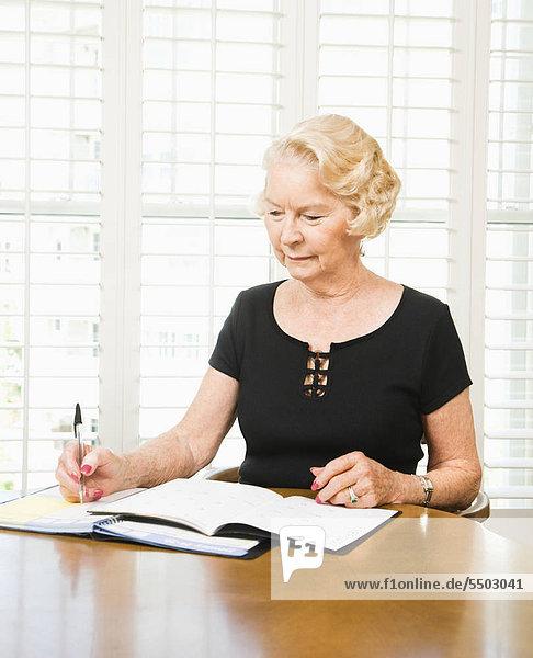 Caucasian Frau schreiben im Kalender.