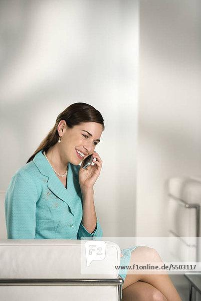 Caucasian erwachsen professionelle Business Woman sitting in modernen Büro auf Handy reden und lächelnd Mitte.