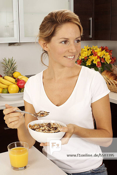 Woman In Kitchen Eating Bowl von Müsli