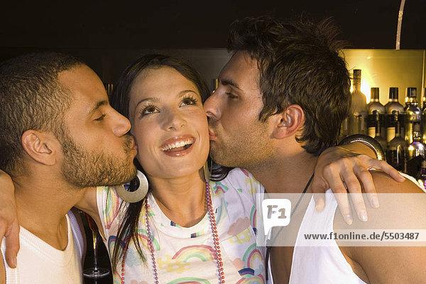 Zwei Männer küssen eine junge Frau