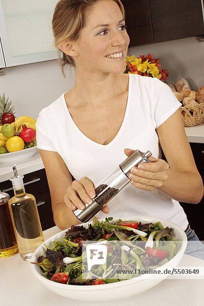 Woman In Kitchen Grinding Pepper On Salad