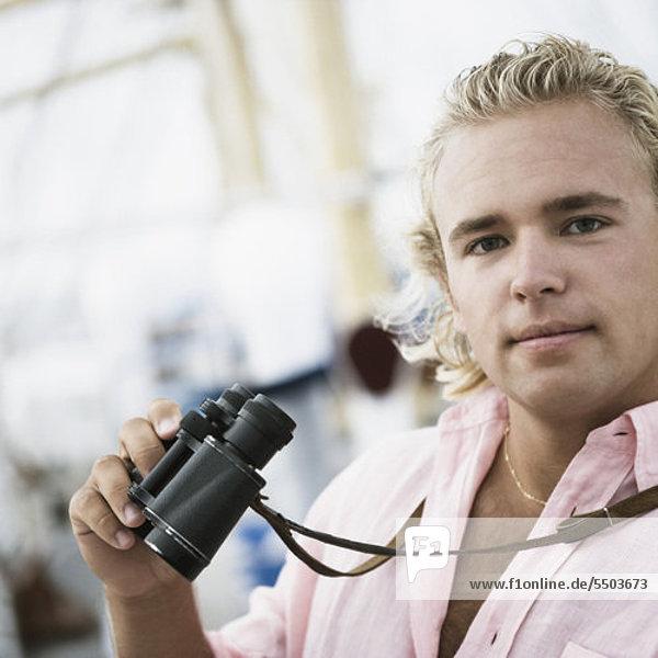 Porträt eines jungen Mannes mit Fernglas