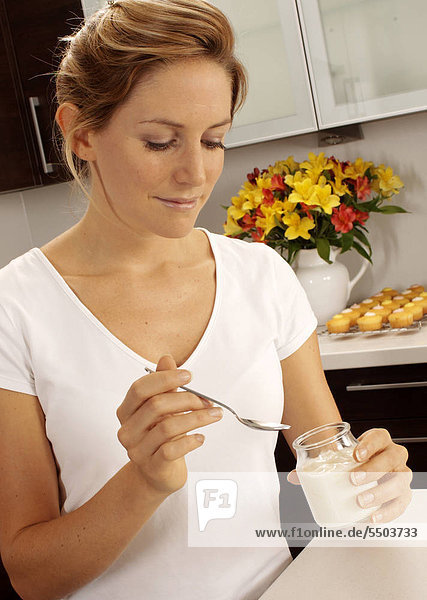 Woman In Kitchen Eating Joghurt