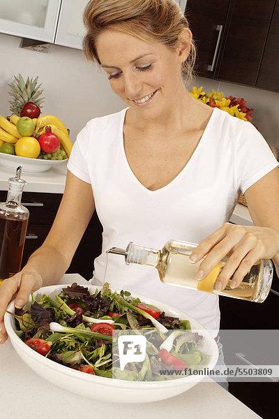 Frau In der Küche Gießen Salat-Dressing auf Salat