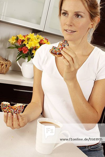 Woman In Kitchen Eating Donut