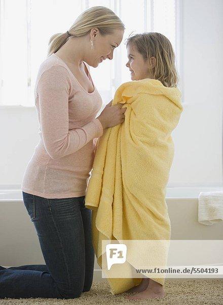 Mutter Lächeln an Tochter umwickelt Handtuch