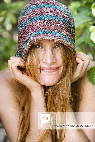 Portrait of pretty caucasian redhead wearing hat.