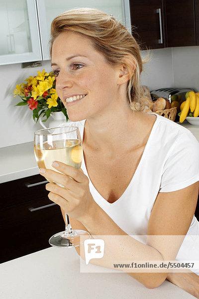 Frau In der Küche trinken Glas Weißwein