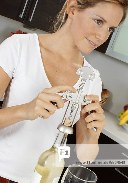Frau In der Küche öffnen Flasche Wein