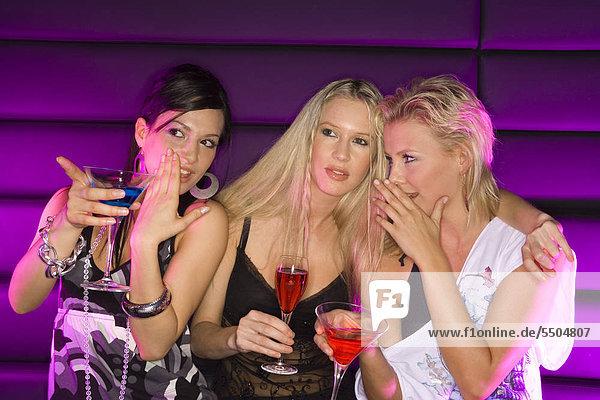 Drei junge Frauen trinken Cocktails