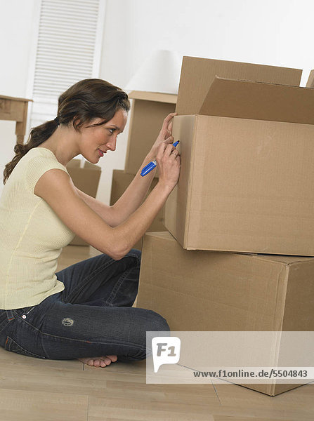 Woman marking boxes on moving day