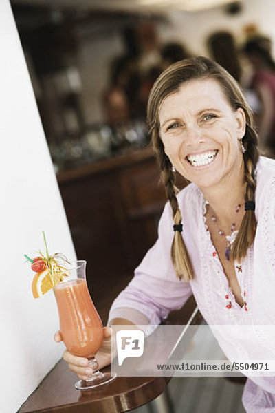 Portrait of a mid adult woman holding a glass of cocktail and smiling
