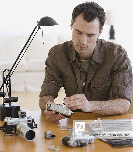 Man assembling camera at table
