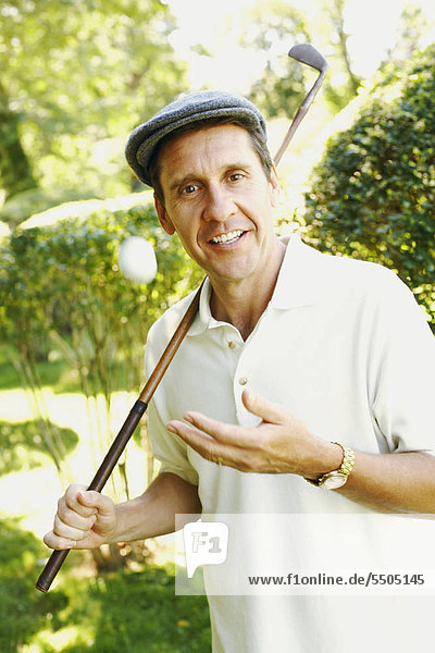 Portrait of a mature man holding a golf club and smiling