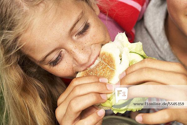 A boy feeding a girl a burger.