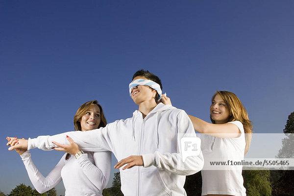 Drei Jugendliche spielen Blinde Kuh