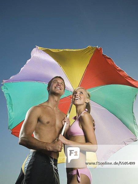 Couple Standing unter Sonnenschirm