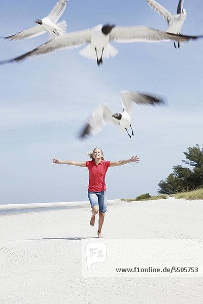Mädchen jagen Vögel am Strand