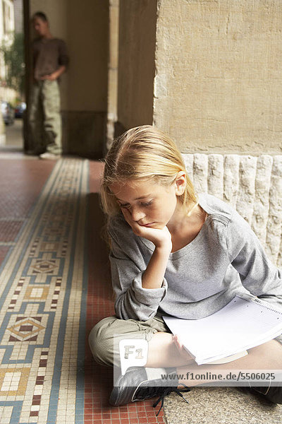 A sad girl sitting on the ground