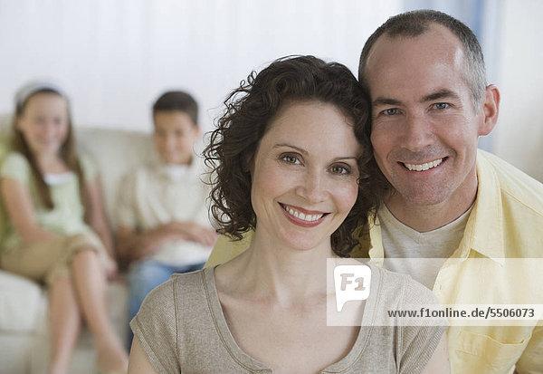 Eltern mit Kindern im Hintergrund