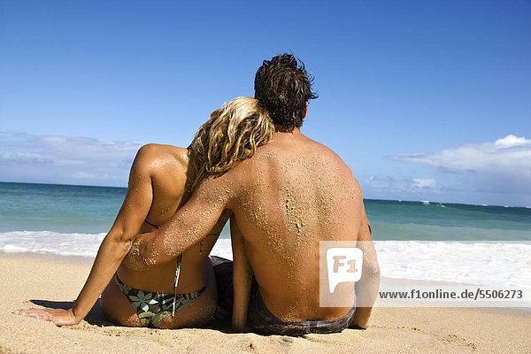Rückansicht des Paares sitzen auf Maui  Hawaii Strand mit Frau schiefen Kopf auf Schulter des Mannes.