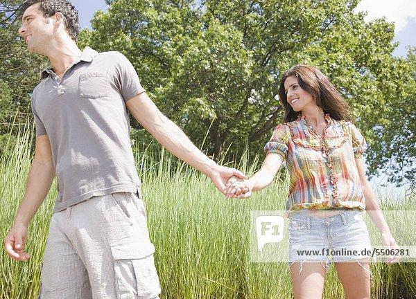 Paar Hand in Hand und zu Fuß durch Schilf