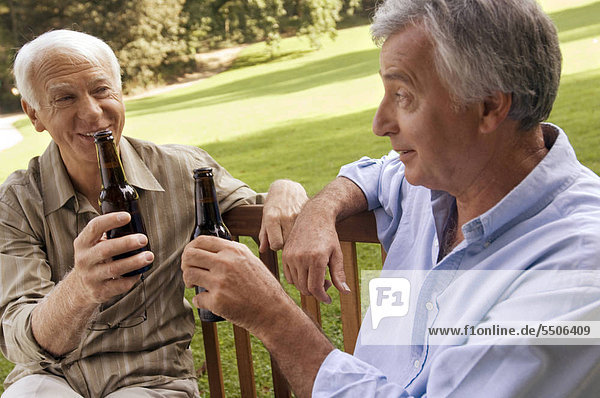 Two elderly men having beer.