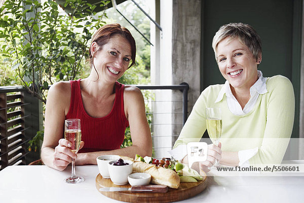 Portrait of two mature women holding champagne flutes and smiling