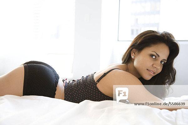 Hispanische young adult woman ärztin in Dessous liegen auf dem Bett und Blick auf Viewer.