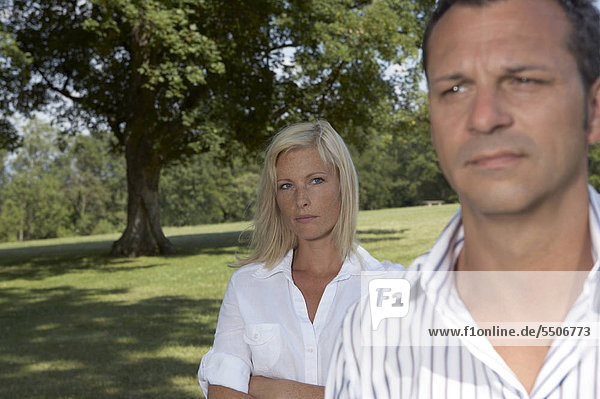 Junges Paar mit ernsten Gesichtern im Park