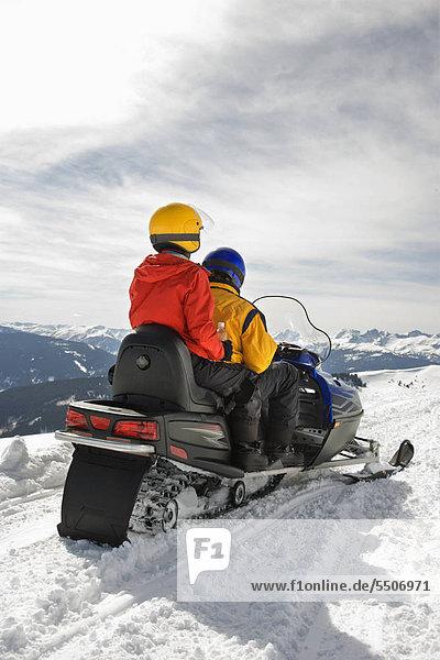 Mann und Frau Reiten auf Motorschlitten in verschneitem gebirgigen Gelände.