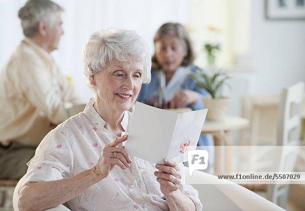 Senior Senioren Frau grüßen Karte vorlesen