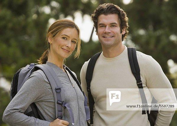 Paar tragen Rucksäcke in Wäldern