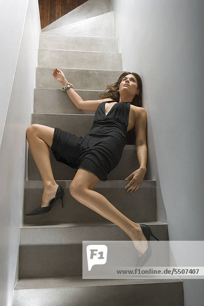 Frau im Abendkleid liegt leblos auf Treppe
