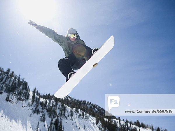 Man on snowboard in air  Wasatch Mountains  Utah  United States