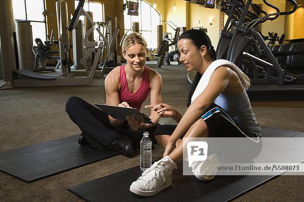 Erstklassige Fröhlichkeit Caucasian Frau mit personal Trainer im Fitnessstudio.