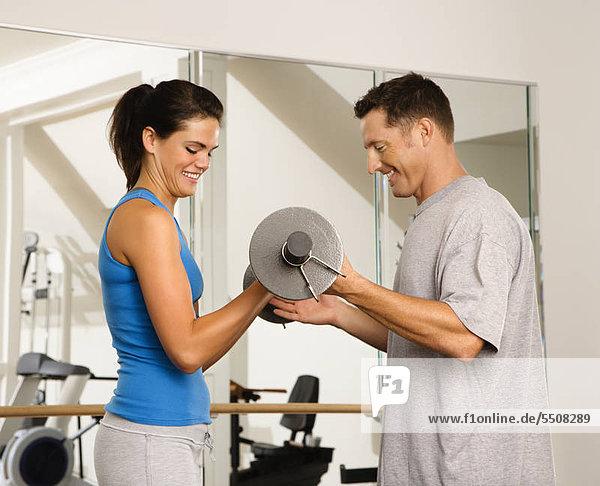 Mann und Frau in Gym Gewichte zu heben.