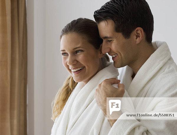 Paar in Bademänteln umarmt sich