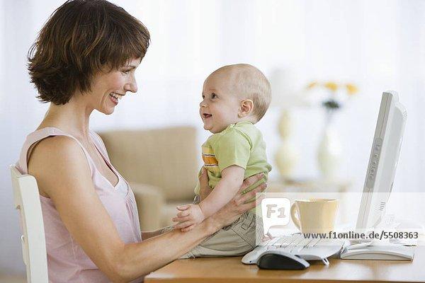 Mutter und Baby lächeln einander