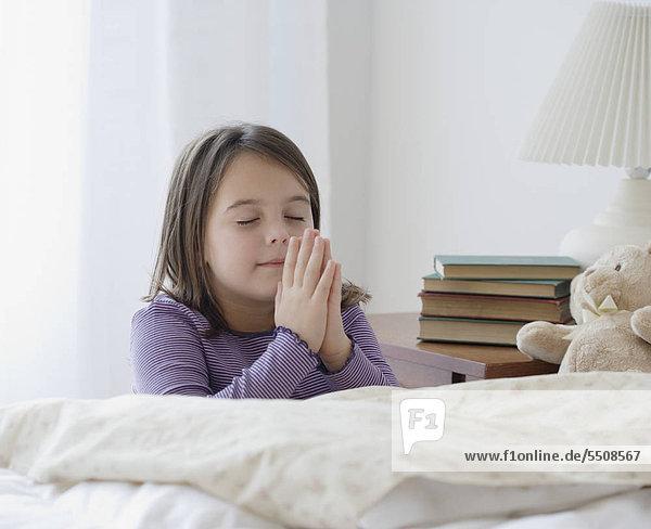 Girl praying next to bed