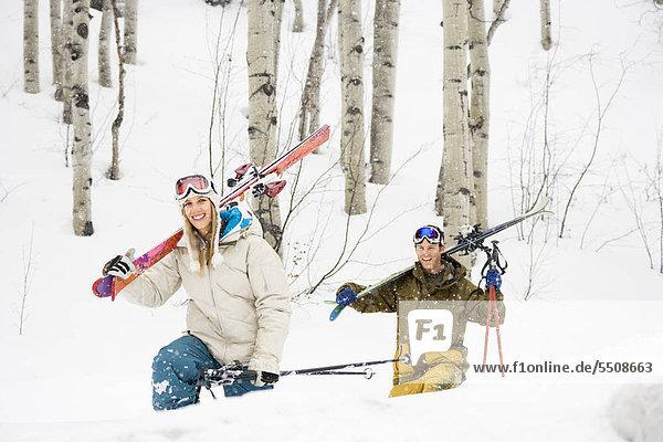 Happy young Couple Spaziergang durch Schnee Ski über lächelnd tragen.