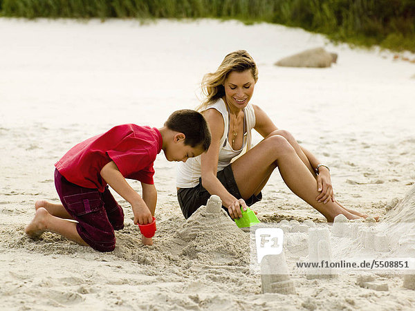 Mutter und Sohn bauen eine Sandburg