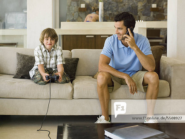 Boy playing playstation  father on the phone.