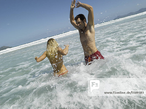 Mid adult couple splashing water in the sea