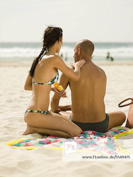 Woman applying suntan lotion on her boyfriend.