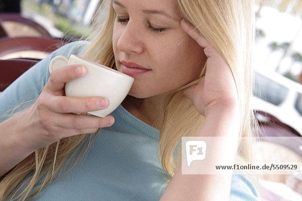 Young blond Woman enjoying Tasse Kaffee mit den Augen geschlossen  Porträt