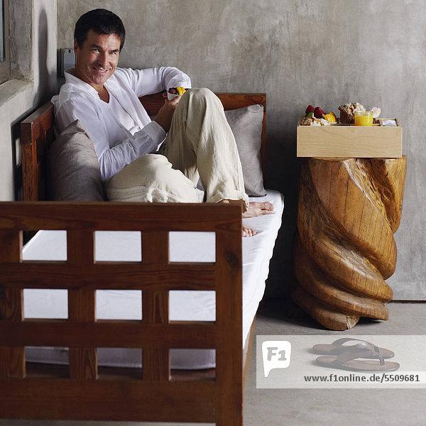 liegend liegen liegt liegendes liegender liegende daliegen Portrait Mann Lebensmittel Schüssel Schüsseln Schale Schalen Schälchen halten Bett reifer Erwachsene reife Erwachsene zurücklehnen